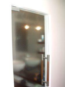 szklane drzwi z metalową klamką